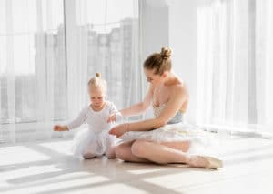 Mother cuddling with her little daughter is sitting on the floor in dance studio. Young ballerina in tutu hugging her little daughter
